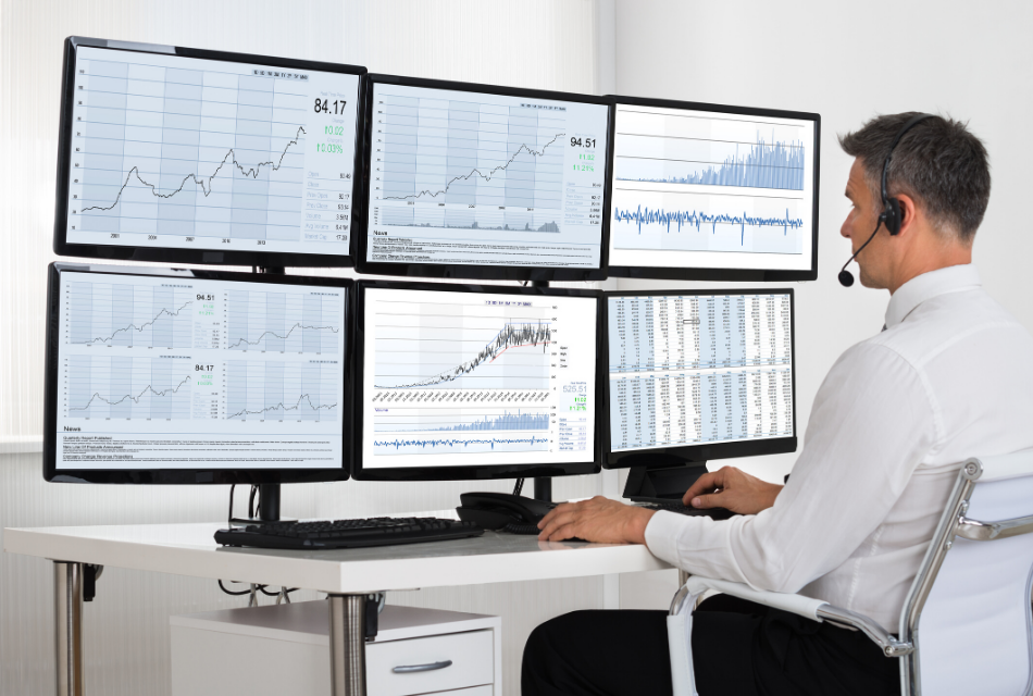 mężczyzna siedzący przy 6 monitorach, śledzi różne wykresy
