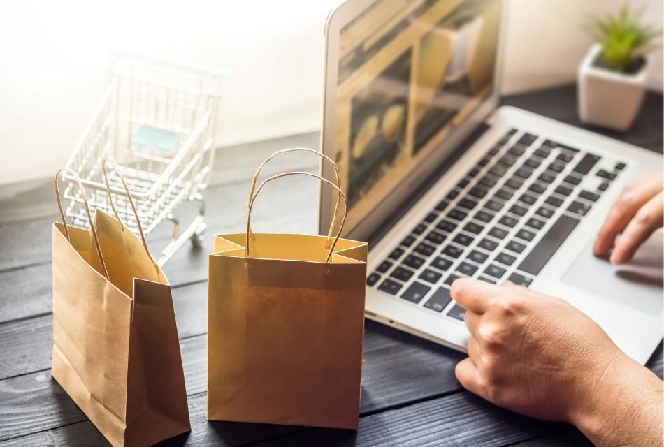 mężczyzna siedzący przy laptopie, obok małe papierowe torby