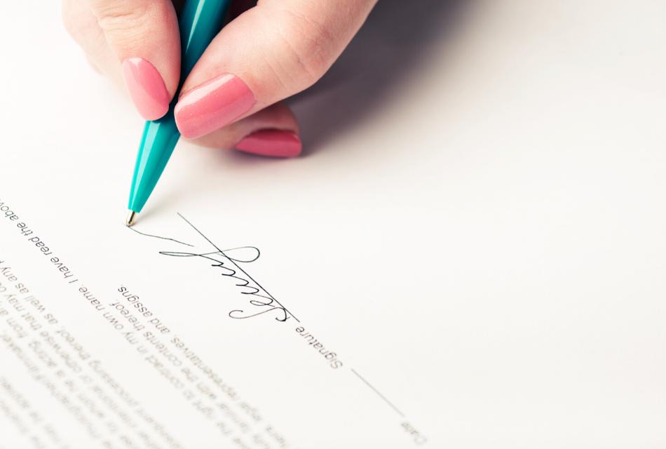 kobieta składa na umowie swój podpis