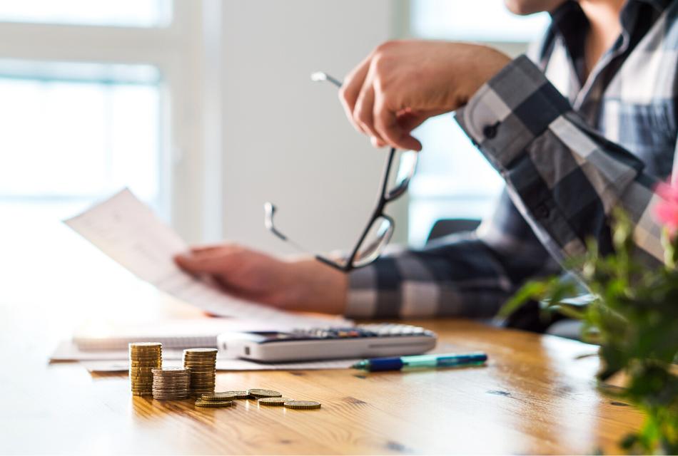 mężczyzna siedzący przy stole nad dokumentem, obok niego leżą pieniądze