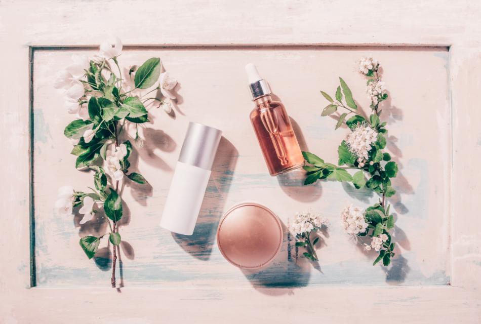 3 kosmetyki w otoczeniu kwiatów, leżące na stole
